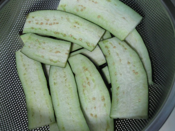 Eggplant sliced, salted, and set to drain in a colander