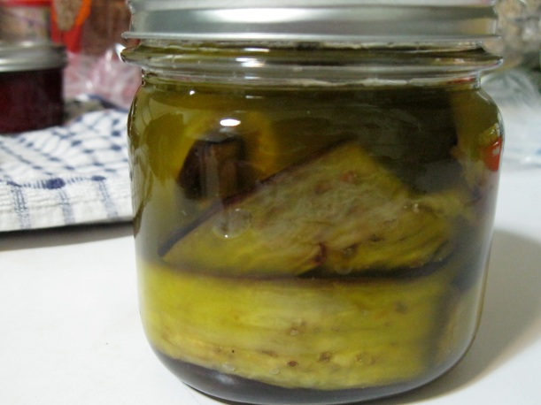 Eggplant packed into a jar and covered in oil mixture.