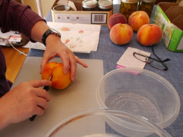 Slicing the blanched peaches. It's actually easiest to peel them first and then slice them.